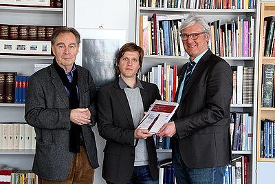 Georgios Kontos (Mitte) überreicht den Mollerband an Oberbürgermeister Jochen Partsch. Links Jochen Rahe
